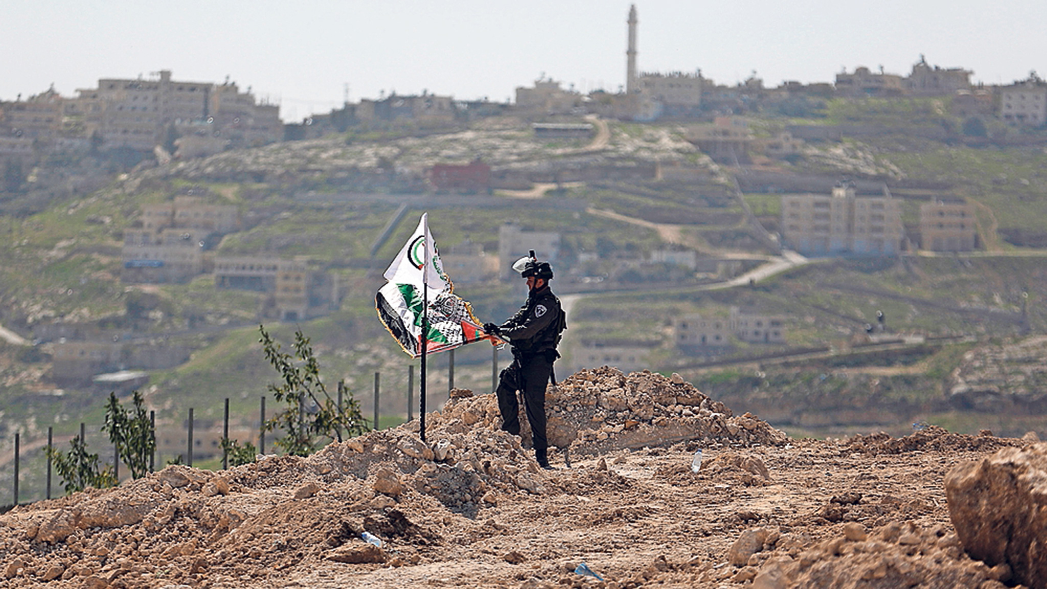 An Israeli border policeman removes a Palestinian flag and a Fatah flag during a protest against what Palestinians say is land confiscations by Israel for Jewish settlements, near the West Bank town of Abu Dis near Jerusalem March 6, 2015