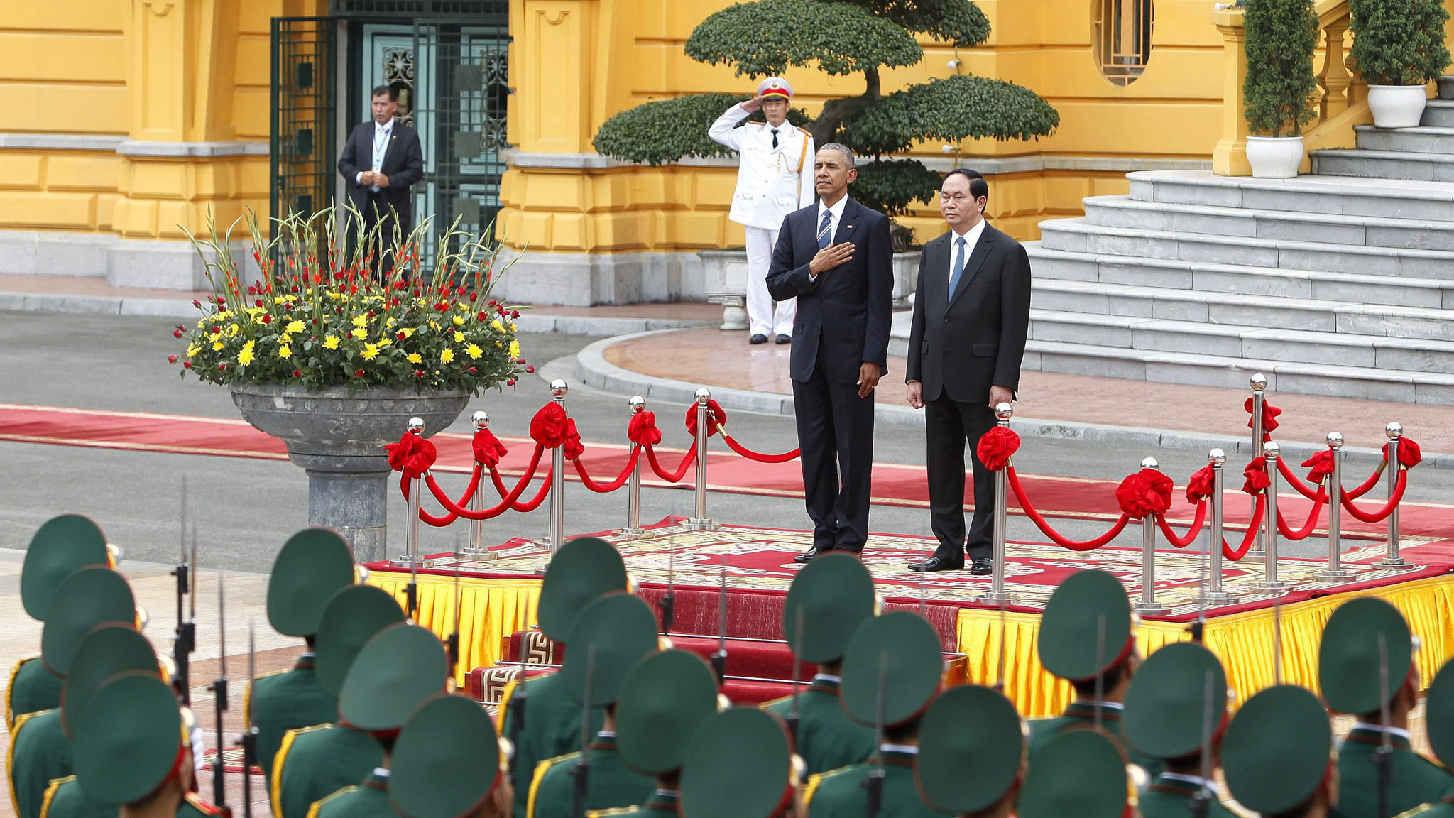 epa05324585 US President Barack Obama (C-L) and Vietnam's President Tran Dai Quang (C-R) review an honor guard at the Presidential Palace in Hanoi, Vietnam, 23 May 2016. US President Barack Obama visits Vietnam for the first time from 23 to 25 May 2016, making him the third US President to visit the South East Asian country since the end of the Vietnam War in 1975. During the first day of his visit Obama announced that the US will lift its arms embargo on weapon sales to Vietnam. EPA/MINH HOANG