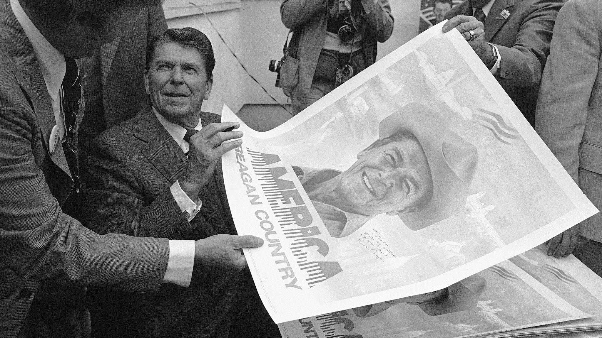 Republican Presidential candidate Ronald Reagan hands autographed campaign poster to unidentified supporter during stop in Pasadena, California, Tuesday, May 27, 1980. Reagan, a former California governor, is campaigning for his home state's on June 3 primary. (AP Photo/Zeboski)